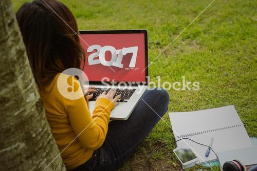 Composite image of woman using laptop in park