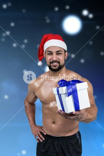 Composite image of muscular man in santa hat