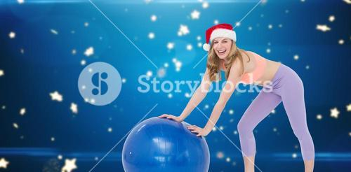 Composite image of festive blonde woman using exercise ball