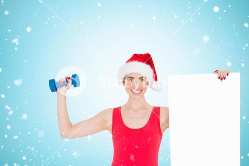Composite image of festive fit brunette holding page and dumbbell