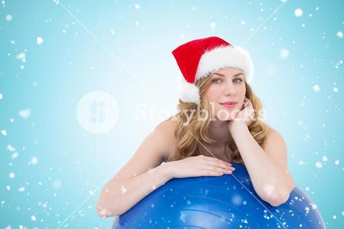 Composite image of festive fit blonde leaning on exercise ball