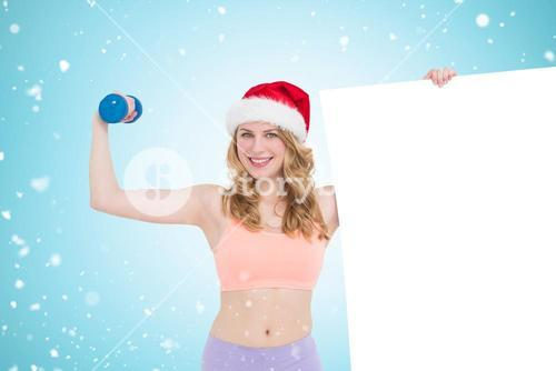 Composite image of festive fit blonde smiling at camera holding poster