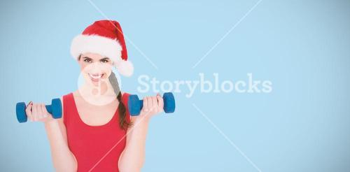 Composite image of festive fit brunette holding dumbbells