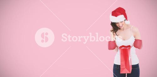 Composite image of happy brunette in boxing gloves looking in shopping bag