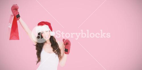 Composite image of festive brunette in boxing gloves with shopping bag