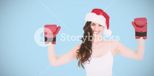 Composite image of festive brunette in boxing gloves with arms raised