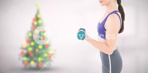 Composite image of fit woman lifting dumbbell