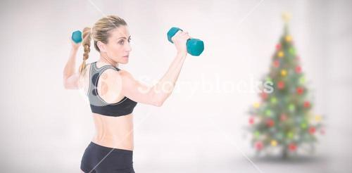 Composite image of female bodybuilder holding two dumbbells with arms up