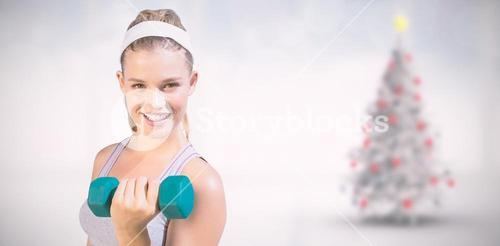 Composite image of sporty happy blonde lifting dumbbell on the beach