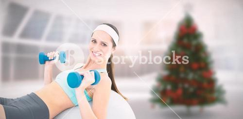 Composite image of smiling fit woman exercising with dumbbells on fitness ball