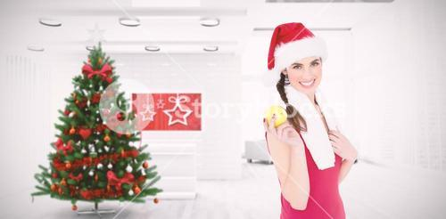Composite image of festive fit brunette holding apple