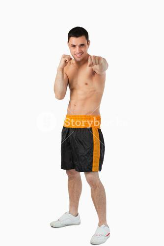Young boxer with bare fists striking straight