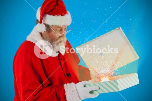 Composite image of santa claus looking at open gift box