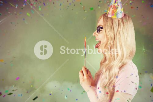 Composite image of side view of a beautiful hipster holding a giant lollipop