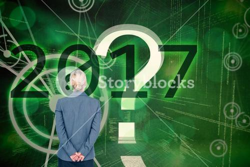 Composite image of businesswoman standing with hands behind back