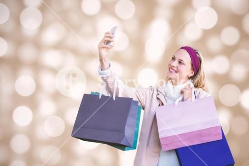 Composite image of smiling woman with shopping bags taking selfies