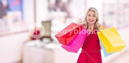 Composite image of stylish blonde in red dress holding shopping bags