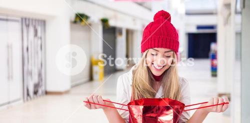 Composite image of pretty blonde opening gift bag