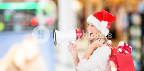 Composite image of festive blonde holding megaphone and bags