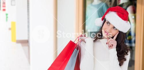 Composite image of festive brunette holding shopping bags and thinking