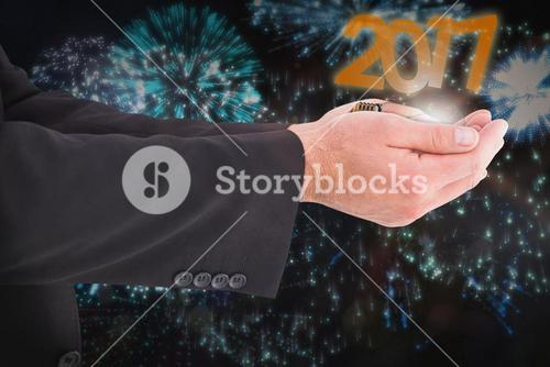 Composite image of businessman holding something with his hands