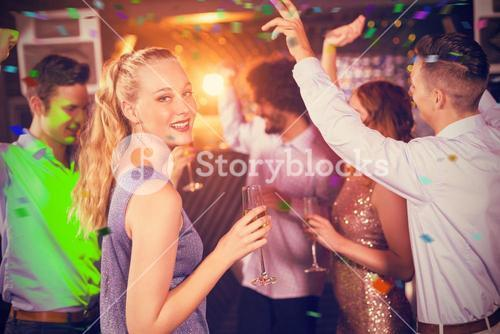 Composite image of woman holding glass of champagne while dancing with friends