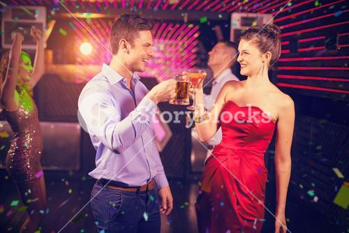 Composite image of smiling couple toasting glass of beer and cocktail
