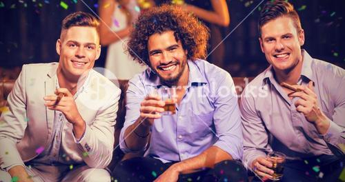 Composite image of three happy friends having cigar and whisky in bar