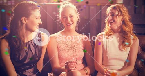Composite image of three female friends holding shot glass of tequila in bar