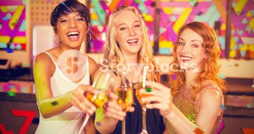 Composite image of portrait of three smiling friend toasting glass of champagne