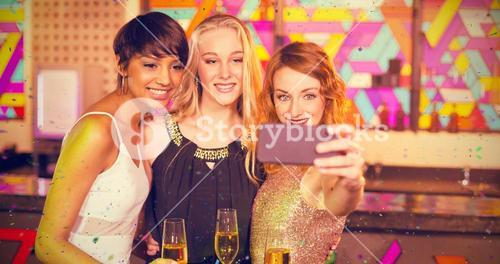 Composite image of female friends taking selfie from mobile phone while having champagne