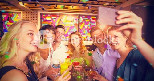 Composite image of group of friends taking selfie from mobile phone while having cocktail