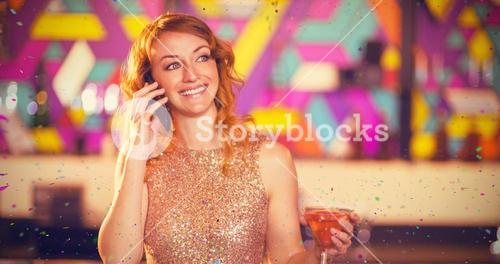 Composite image of young woman talking on mobile phone while having cocktail at counter