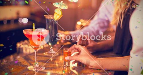 Composite image of friends holding glass of tequila shot in bar