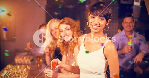 Composite image of portrait of friends having tequila in bar
