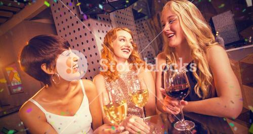 Composite image of smiling friend having glass of champagne