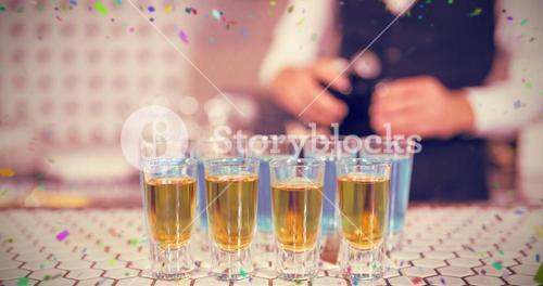 Composite image of glass of blue lagoon drinks and whisky on bar counter