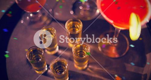 Composite image of cocktail drinks and shot glasses of tequila on serving tray