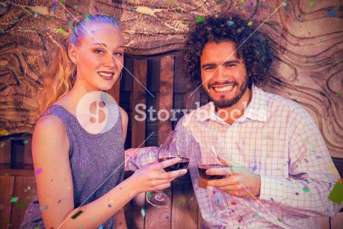 Composite image of couple toasting glass of wine in bar
