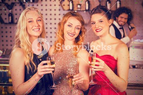 Composite image of portrait of smiling friends having glass of champagne