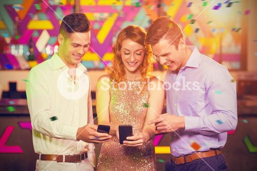 Composite image of smiling friend looking at mobile phone