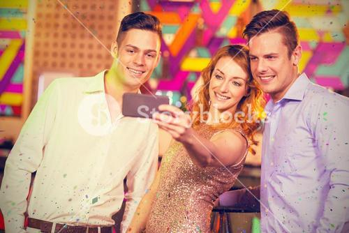 Composite image of smiling friends taking a selfie from mobile phone