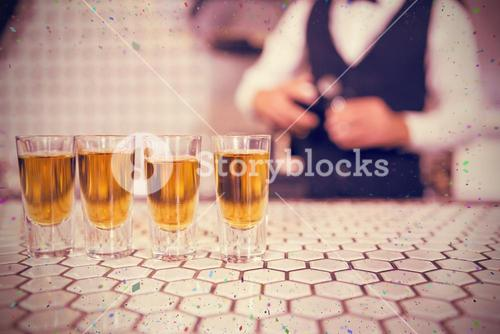 Composite image of glasses of whisky on bar counter