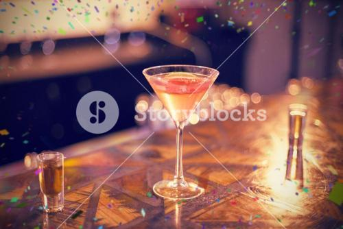 Composite image of cocktail glass and tequila shot glass on counter