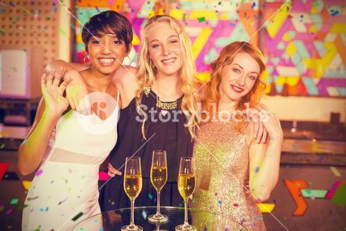 Composite image of portrait of smiling female friends standing with arm around in bar