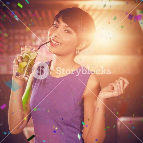 Composite image of young woman dancing on dance floor while having cocktail