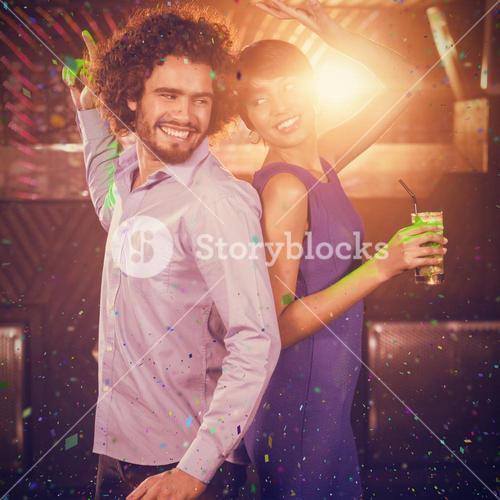 Composite image of cute couple dancing together on dance floor while having drink