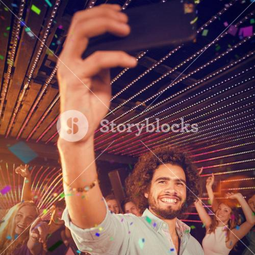Composite image of man taking a selfie from mobile phone while friends dancing on dance floor