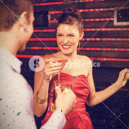 Composite image of smiling couple holding glass of beer and cocktail while dancing