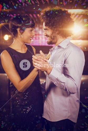 Composite image of cute couple dancing together on dance floor